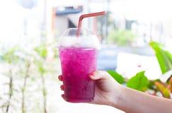 Women Handle holding Ice water italian soda purple in plastic cup stock image