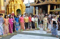 Women handling brooms with honour. Woman handdle brooms inside sacred site of budhist diversity in Yangon, Burma, Myanmar.nPublic gathering site of meditation Royalty Free Stock Photos