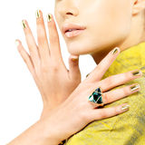 Women hands with golden nails and precious stone emerald. Women hands with golden nails and green precious stone emerald - isolated on white background royalty free stock photography