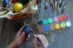 Women hands holding brushe and easter egg for coloring. Women hands holding Brushe  and easter egg for coloring Stock Image
