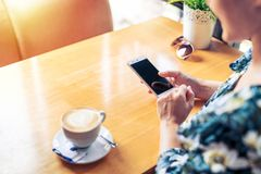 Women hands holding mobile phone with blank copy space screen text message content, female read news on cellphone in coffee shop royalty free stock photography