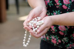 Women hands holding pearl beads jewelery. Closeup of female hand with pearl jewelry. Female hand holding a string of pearl. Royalty Free Stock Photography
