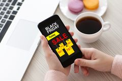 Women hands holding phone with sale black Friday screen Royalty Free Stock Photography