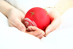 Women hands holding red Christmas Ball. On white background Royalty Free Stock Photography
