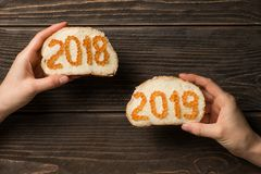 Women hands holding two sandwiches with red caviar in the shape of 2018 and 2019 numbers stock photos