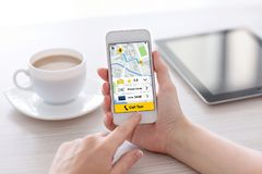 Women hands holding white phone with app call taxi screen Stock Images