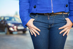 Women hands in jeans pockets and car on background Stock Photos