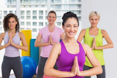 Women with hands joined exercising at gym Stock Photo