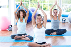 Women with hands joined overhead in lotus pose Royalty Free Stock Photo