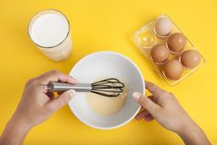 Women Hands Mixing Baking Ingredients eggs and Milk in Bowl Dessert Preparation Yellow Background Top View stock photo
