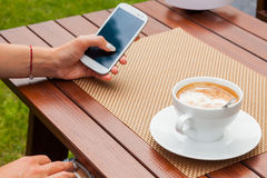 Women hands with mobile phone coffee on the table. Outdoor photo Stock Photo