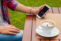Women hands with mobile phone coffee on the table. Outdoor photo Royalty Free Stock Photography