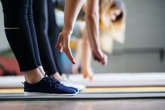 Women hands stretching to toecaps on group workout stock photo