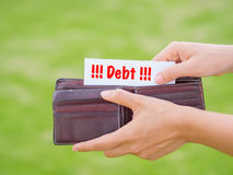 Women Hands taking out debt paper from wallet. On the green grass field Stock Photography
