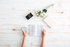 Women hands turn over book pages on the wooden desk Royalty Free Stock Images