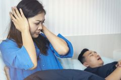 A woman has a nuisance to the man he loves sleeping loud snoring. A women has a nuisance to the men he loves sleeping loud snoring.Concept of life together stock photos