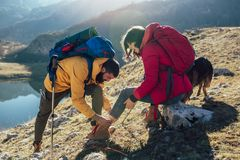 Woman has sprained her ankle while hiking, her friend uses the first aid kit to tend to the injury. A women has sprained her ankle while hiking, her friend uses stock photography