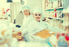 Women with hats selling nuts and pastry in shop royalty free stock photography