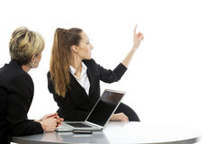 Women having a business meeting. Two women during a business meeting with laptop on white background studio Royalty Free Stock Image