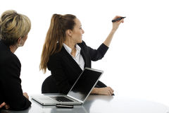 Women having a business meeting. Two women during a business meeting with laptop on white background studio Stock Images