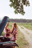 Women having car problem. Two young women having car problem on country road Royalty Free Stock Photography