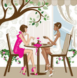Women having coffee. A white and a black woman sitting at a cafe, talking while having a coffee Stock Photos