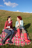 Women having country picnic. Smiling at each other Royalty Free Stock Photography