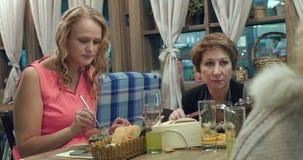 Women having dinner at the restaurant stock video