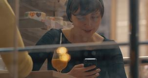 Women having friendly meeting in cafe and being attracted with mobiles. Two female friends meeting in the cafe, but they are not even talking as being busy with stock video footage