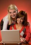Women having fun. Two beautiful women having fun working with on laptop Royalty Free Stock Photography
