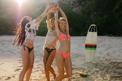 Women having fun on the beach party. Happy female friends partying on the beach and dancing. Women having fun on the beach party Stock Photo