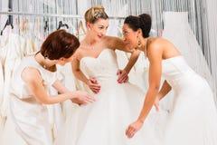 Women having fun during bridal dress fitting in shop. Women having fun during bridal gown fitting in wedding fashion store Stock Photos
