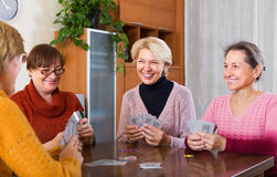 Women having fun with cards. Happy elderly women having fun with pack of cards indoor Stock Photography