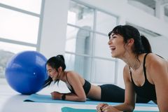 Women having fun during fitness training. Fit girls smiling while exercising together in gym. Healthy young women having fun during fitness training Stock Photography