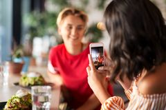 Women having lunch and photographing at cafe royalty free stock photography