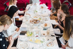 Women having meeting bluer soft focus. Bluer soft focus Women sitting at long table on meeting and communicating. French breakfast, French lesson for adults royalty free stock images