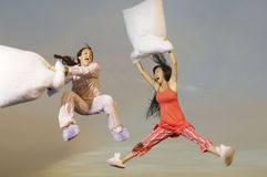 Women Having Pillow Fight Midair. Two multiethnic young women having pillow fight midair outdoors Stock Photography