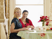 Women Having Tea At Dining Table. Portrait of two smiling young women having tea at dining table Stock Images