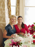 Women Having Tea At Dining Table. Portrait of two smiling young women having tea at dining table Royalty Free Stock Image
