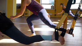 Close-up of working out with suspension straps. Women having training with TRW fitness straps in a gym in slow motion. Healthy style concept stock video