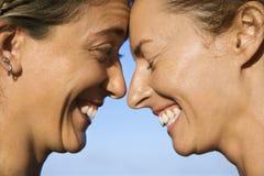 Women head to head smiling. stock photo