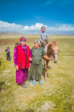 Women with headcloth in Kyrgyzstan. Son Kol, Kyrgyzstan - circa September 2011: Native women dressed in skirts and with headcloths pose in Son Kol, Kyrgyzstan Royalty Free Stock Images