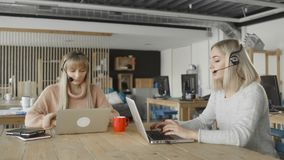 Women with headphones with microphone talks to a customers via computer. Women with pc communicates through skype. 4K stock footage