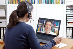 Women headsets video consultation counselor. Woman with headset at her desk in front of her laptop having an online call with her therapist, text space stock photography