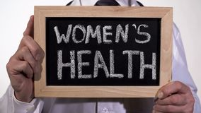 Women health written on blackboard in gynecologist hands, reproductive medicine. Stock footage stock photography