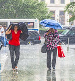 Women in heavy rain. NEW YORK, USA - JULY 8, 2010: women in heavy rain in New York. With 100 mm the average railfall the July is the most wet day of a year in Stock Image