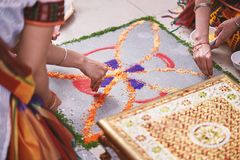 Women help coloring the traditional rice art Rangoli on the floor for indian wedding. Women helps coloring tradition colorful rice art or sand art Rangoli on the Royalty Free Stock Photos