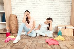 The woman and her daughter rest after tiring the house. They sit on the floor with their backs against the wall and rest. The women and her daughter rest after Stock Image
