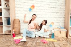 The woman and her daughter rest after tiring the house. They sit on the floor with their backs against the wall and rest. The women and her daughter rest after Stock Photo