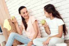 The woman and her daughter rest after tiring the house. They sit on the floor with their backs against the wall and eat. The women and her daughter rest after Stock Photos